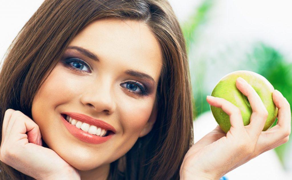 фото девушки с красивыми зубами и яблоком. Чтобы зубы были здоровыми, а улыбка сияющей, ученые провели несколько испытаний